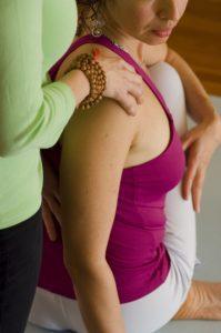 yoga teacher helping student